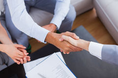 Salesman shaking hands with client. With contract on the coffee table Royalty Free Stock Image