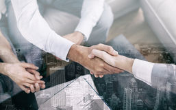Salesman shaking hands with client. With contract on the coffee table royalty free stock photo