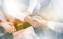 Salesman shaking hands with client. With contract on the coffee table stock photos