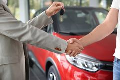 Salesman shaking hands with customer while giving car key in auto dealership. Closeup stock photography