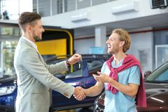 Salesman shaking hands with customer while giving car key royalty free stock images