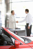 Salesman shaking hands with male customer in car showroom, focus on red convertible in foreground Royalty Free Stock Images