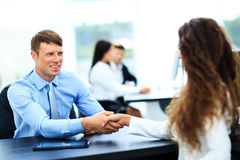 Salesman shaking hands to clients. In the office stock image