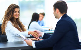 Salesman shaking hands to clients. In the office royalty free stock photo