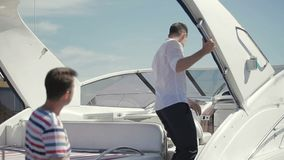 Salesman show buyer a yacht. Salesman show yacht to buyer. Young man ask about details of purchase and characteristics of yacht. Businessmen discuss the details stock footage