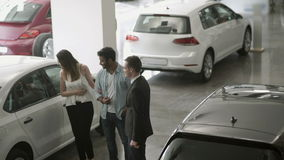 The salesman show the cars to young couple in car dealership. Young couple chooses the automobile in car showroom. Smart manager in suit demonstrates the stock footage