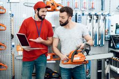 Salesman is showing bearded client new chainsaw explaining details on laptop in power tools store. royalty free stock photography