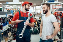Salesman is showing bearded client new giant wrench in power tools store. Salesman in red shirt and baseball cap is showing bearded client new giant wrench in Stock Images