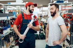 Salesman is showing bearded client new giant wrench in power tools store. Salesman in red shirt and baseball cap is showing bearded client new giant wrench in Royalty Free Stock Image
