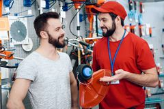 Salesman is showing bearded client new lawn mower in power tools store. Salesman in red shirt and baseball cap is showing bearded client new lawn mower in power Royalty Free Stock Photo