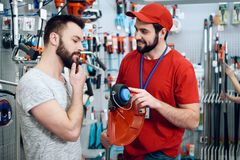 Salesman is showing bearded client new lawn mower in power tools store. Salesman in red shirt and baseball cap is showing bearded client new lawn mower in power stock image