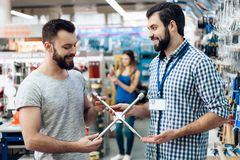 Salesman is showing bearded client new spanners in power tools store. Salesman in checkered shirt is showing bearded client new spanners in power tools store royalty free stock photography