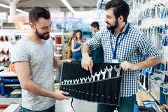 Salesman is showing bearded client set of wrenches in power tools store. Salesman in checkered shirt is showing bearded client set of wrenches in power tools Stock Photography