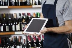 Salesman Showing Blank Digital Tablet In Wine Shop. Midsection of salesman showing blank digital tablet in wine shop stock photography
