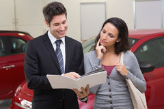 Salesman showing brochure to customer and smiling Stock Image