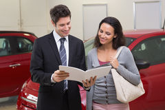 Salesman showing brochure to customer and smiling Royalty Free Stock Image