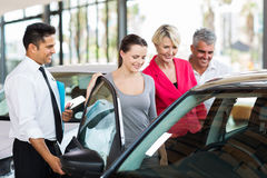 Salesman showing car family. Handsome car salesman showing a new car to a family stock photography