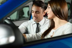 Salesman showing car inside for client. Woman is interisting in buying car. Sales men is going to make a deal stock images