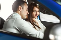 Salesman showing car inside for client. Woman is interisting in buying car. Sales men is going to make a deal stock photos