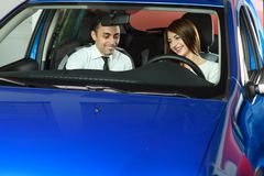 Salesman showing car inside for client. Woman is interisting in buying car. Sales men is going to make a deal stock photography