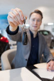 Salesman showing car key while sitting in showroom royalty free stock photo