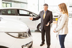 Salesman showing a car to a client. At new car showroom Royalty Free Stock Images