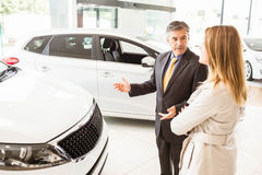 Salesman showing a car to a client. At new car showroom Royalty Free Stock Photography