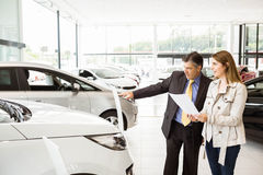 Salesman showing a car to a client. At new car showroom Stock Photography