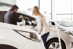 Salesman showing a car to a client. At new car showroom Royalty Free Stock Photos