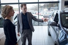 Salesman showing car to female customer in showroom Stock Photos