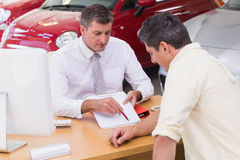 Salesman showing client where to sign the deal. At new car showroom Stock Image