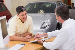Salesman showing client where to sign the deal Royalty Free Stock Photos