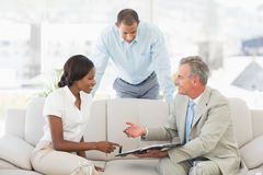 Salesman showing clients where to sign the contract. In the office royalty free stock images