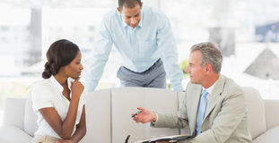 Salesman showing clients where to sign the deal. In the office stock photo