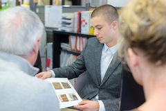 Salesman showing clients wooden parquet samples brochure. Wooden royalty free stock photos