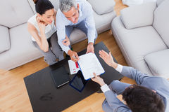 Salesman showing contract to couple who are about to sign stock photo