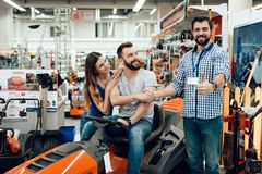 Salesman is showing couple of clients new cleaning machine in power tools store. Two men shaking hands. Salesman in checkered shirt is showing couple of clients stock photos