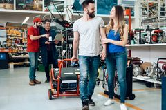 Salesman is showing couple of clients new generator in power tools store. royalty free stock photos