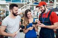 Salesman is showing couple of clients new rubber hammers in power tools store. Salesman in red shirt and baseball cap is showing couple of clients new rubber royalty free stock photography