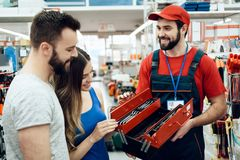 Salesman is showing couple of clients new toolbox in power tools store. Salesman in red shirt and baseball cap is showing couple of clients new toolbox in power Stock Photos