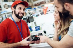 Salesman is showing couple of clients power tool in power tools store. stock image
