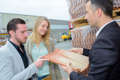 Salesman showing couple modern clay roof tile. Salesman showing couple a modern clay roof tile Royalty Free Stock Images
