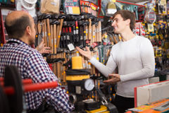 Salesman showing different hammer in supermarket. Smiling salesman showing different tools and instruments in supermarket Royalty Free Stock Photo