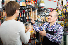 Salesman showing different tools. Happy salesman showing different tools and instruments in supermarket Stock Images
