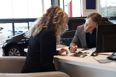 Salesman showing document to customer in car showroom royalty free stock image