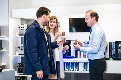 Salesman Showing Espresso Cups To Couple In Hypermarket Stock Image