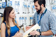 Salesman is showing female client putty spatula in power tools store. Salesman in checkered store is showing female client putty spatula in power tools store stock image