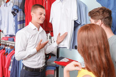 Salesman showing items in shop Royalty Free Stock Photos