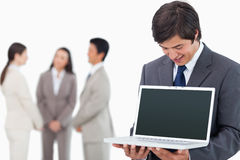 Salesman showing laptop screen with team behind him Stock Photos