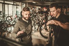 Salesman showing a new bicycle to interested customer in bike  shop. Royalty Free Stock Images